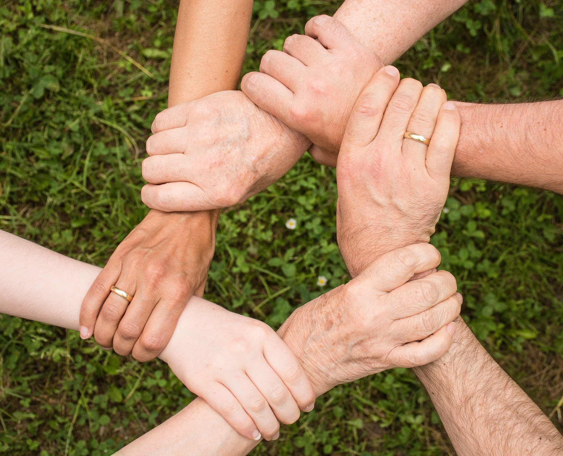 People linking wrists together in a circle
